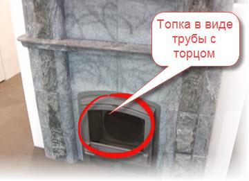 Финская печь-каменка. Топка выполнена в виде трубы. Через панорамное стекло видно, что размер трубы меньше визуального